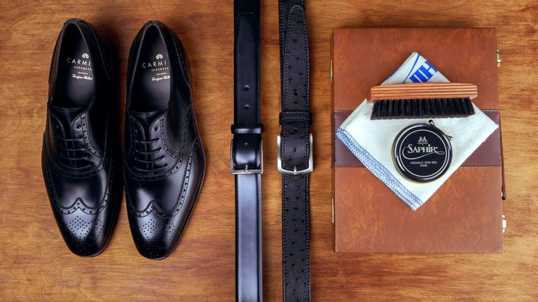 Guide Essential Belts. A picture taken from above and down, showing a pair of black shoes from Carmina, a black leather belt from Andersons, a ostrich belt from Canali and a shoebox in leather with a brush and towel on it