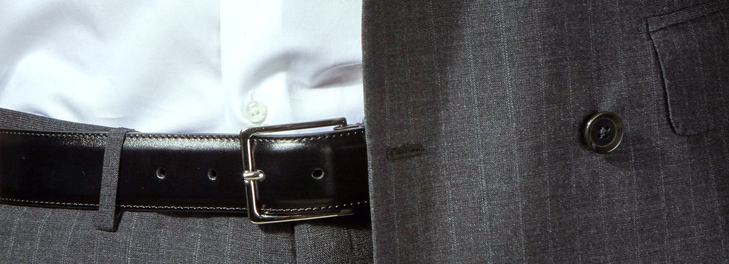 Guide Essential Belts. A picture of a grey ringjacket suit, a white shirt from Stenströms and a black plain woven leather belt from Andersons