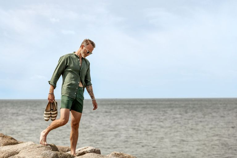 A picture of a fashion model walking on the rocks of a swedish beach with clothes from Eton, Castaner and The bespoke dudes eyewear.