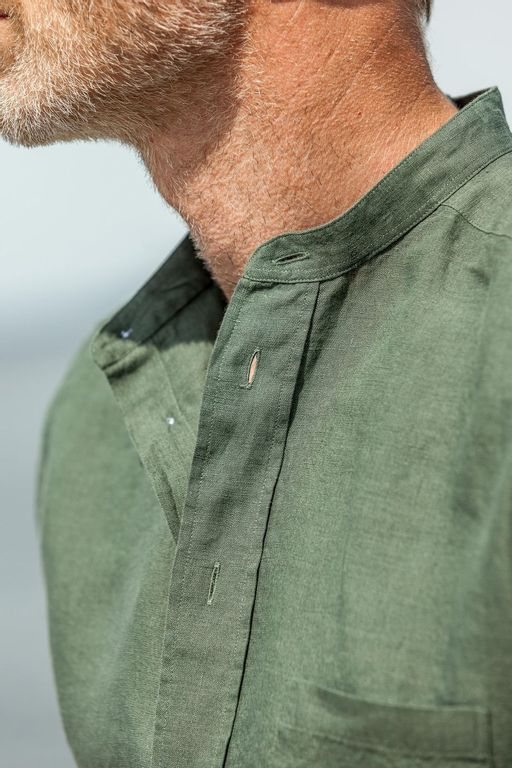 A closeup picture of a swedish model standing by the sea with a green shirt from Eton