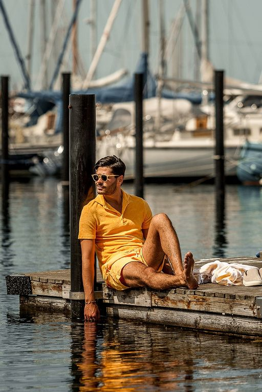 Gabriel hanging out by the pier in a yellow toweling polo and matching madeira swim shorts