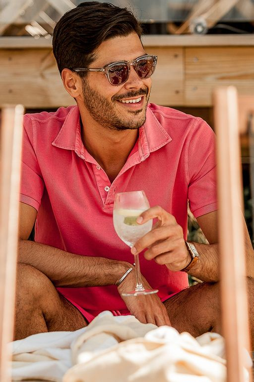 Gabriel hanging out by the seaside bar drinking in a coral washed pique polo and matching Madeira Swim Shorts