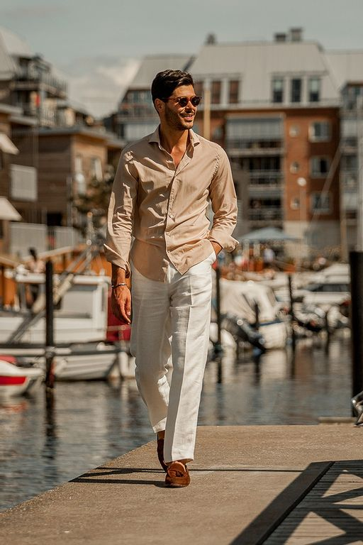 Gabriel walking by the pier wearing a beige beach shirt together with white linen trousers and brown suede loafers