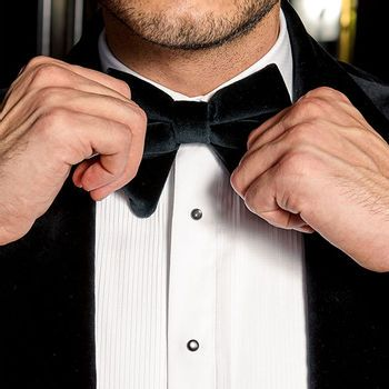 hands fixing a velvet bowtie with tuxedo