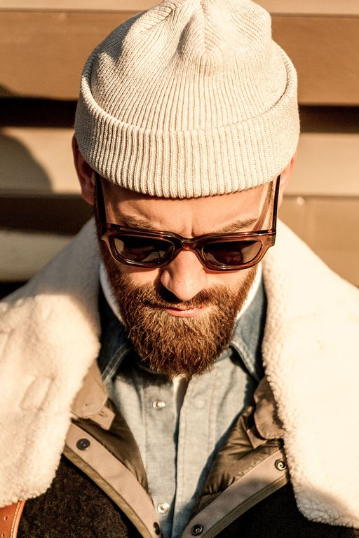 bearded man wearing a shearling jacket, cashmere beanie and sunglasses