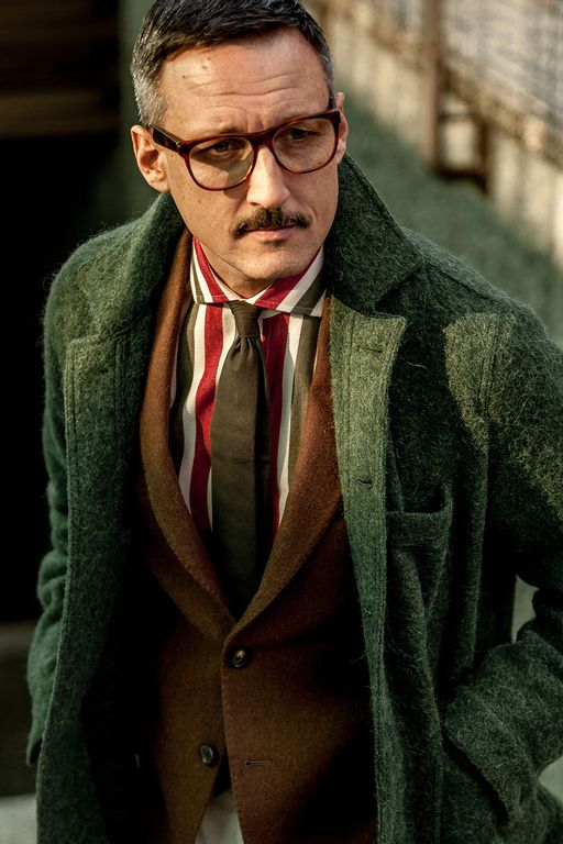 man with moustache wearing a brown blazer and green coat