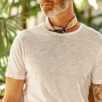 model wearing a white cotton and linen blend t-shirt from Sunspel with a bandana